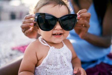 Mom puts big sunglasses on an enthusiastic little girl Imagens