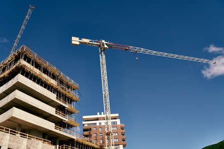 Tower cranes stand on the construction site Imagens