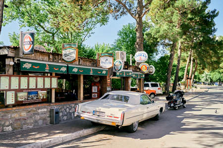 Motorcycle and car stand near the bar in the park Imagens
