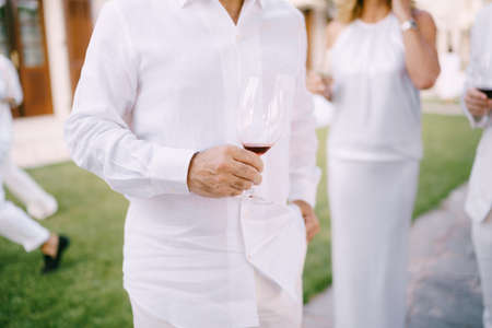 Man in a white shirt and trousers stands with a glass of red wine in his hand Imagens