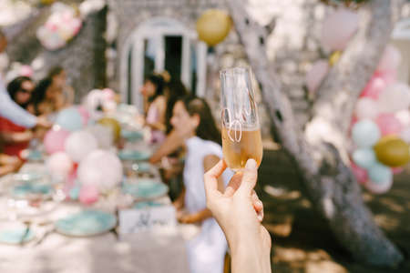 Glass of champagne in hand against the background of a served table with guests Imagens