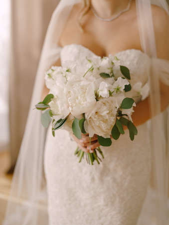 Bride with a bouquet of peonies stands in a wedding dress