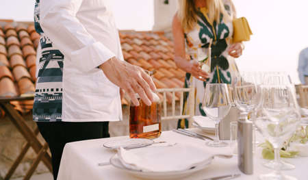 Man stands near a served table and holds a bottle of alcohol with his hand against a background of a woman with an empty glass Imagens