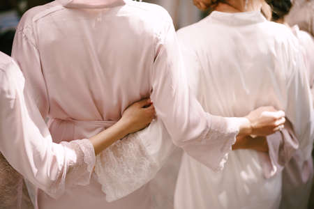 Bridesmaids in robes are hugging each other. Back view Imagens
