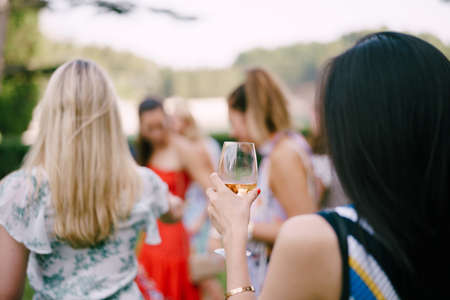 Women with drinks in glasses stand in nature