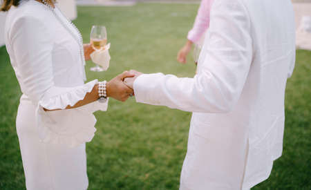 Woman with a glass in her hand holds man hand while standing on a green lawn