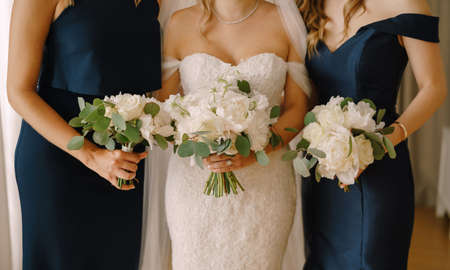 Bride with bridesmaids stand in dresses with bouquets of peonies