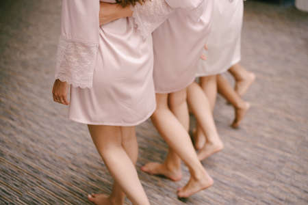 Bridesmaids in robes are walking across the floor Imagens