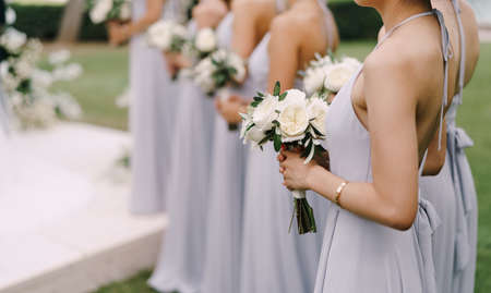 Bridesmaids in dresses stand with bouquets of flowers in a row