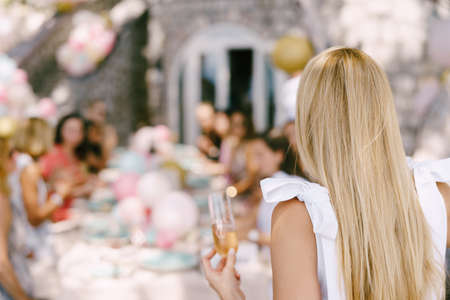 Glass of champagne in girl hand against the background of a served table with guests