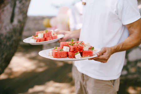 Waiter carries slices of watermelon with cheese and herbs on the plates