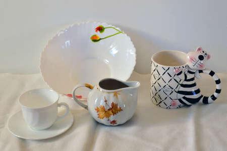 the milk jug: Still life on white . Tableware. Mug, saucer, mug-tiger dish, milk jug.