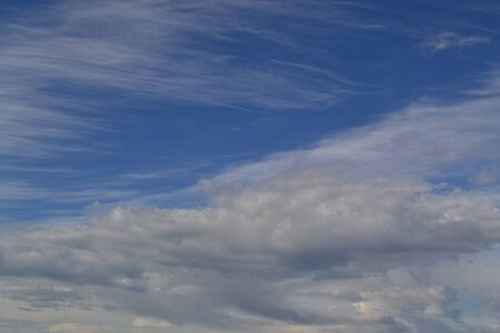 diagonally: Cirrus and Cumulus white clouds on the blue sky background.