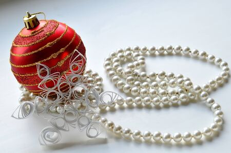 quilling: Christmas composition. Red Christmas ball, beads and a paper snowflake in the style of quilling. Stock Photo