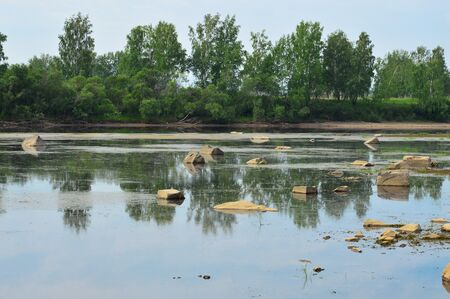 decreased: Summer landscape. Large rocks jut out of the water. The water level in the river decreased.