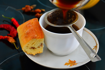 Breakfast. Black coffee with fish cake. Coffee poured into a Cup through a sieve.