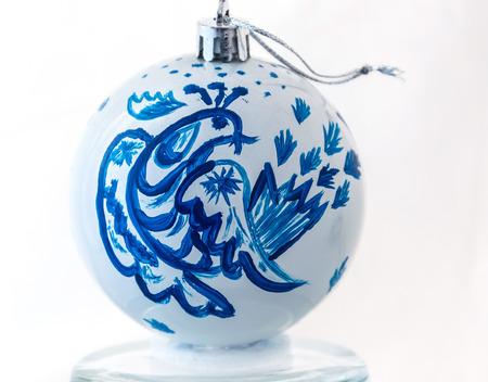Handmade Christmas ball. Blue Firebird on a white background. Fabulous bird.