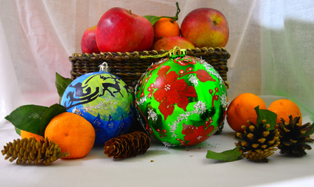 Christmas still life of fruit, balls and cones. On light background. 스톡 콘텐츠