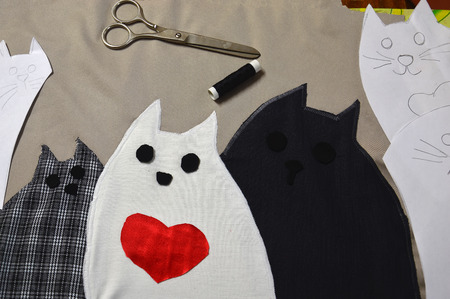 Applique fabric. Multicolored cats from scraps.Production of paper and fabric patterns.