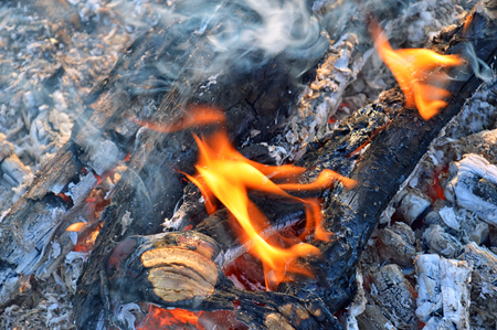 Fire with black coals, orange flames, blue smoke and gray ash. The view from the top. 스톡 콘텐츠