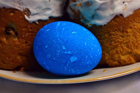 Painted Easter egg and cakes on a plate. Close-up. Bright blue mottled egg. Prepared for the holiday.