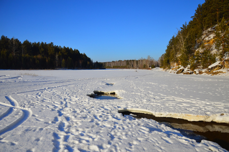 Winter landscape on a clear sunny day. Thaws on the river. Travel to Siberia 스톡 콘텐츠