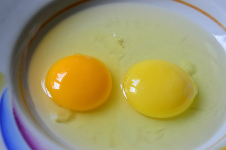 Raw eggs with colorful yolks in a plate. Close-up. 스톡 콘텐츠