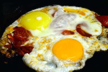 Fried eggs with colorful yolks and tomatoes. In the form of the artists palette. Fried on a black cast iron pan