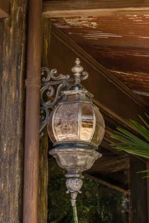 sconce: vintage street light fixture mounted on a wall with decorative details