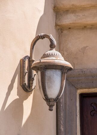 light fixture: old-fashioned nice street light fixture mounted on a wall white decorative details