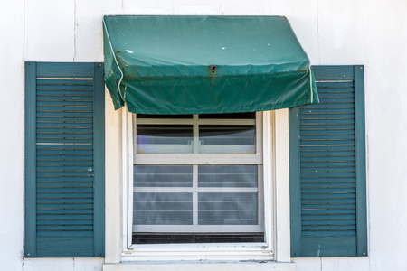 sash: sash window with hunter green simple slope awing tent and shutters Stock Photo