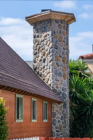 rustic cottage with massive stone chimney Stock Photo