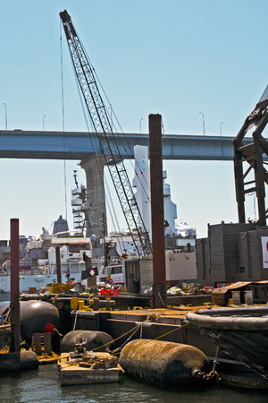 seaport tower crane in front of bridge and floating fenders Imagens