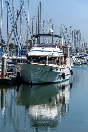 dinghies: moored boat and its reflection in marina