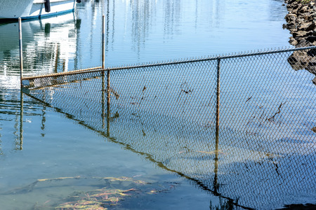 drowned: bay wire mesh fence partly drowned in water and its reflection
