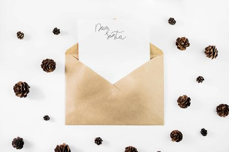Letter for Santa Claus on a white background in an envelope from craft paper surrounded by coniferous branches, cones and gifts. New Year and Christmas concept. Top view, flat lay. Mockup, copy space for your text. Stock Photo