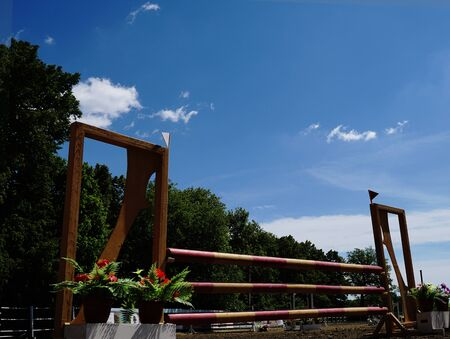 Equestrian sporting competition. Wooden barrier No horse. Against the background of green forest and blue sky.