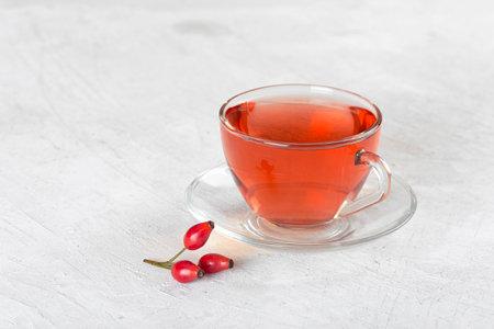 Rosehip tea, medicinal rosehip tea in glass mug gray background