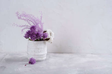 Beautiful bouquet of lavender and cotton on the table. Dried flowers are white-lilac. Copy space. Place for text. Gray textured background.