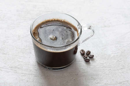 Black coffee in a transparent mug on a light background