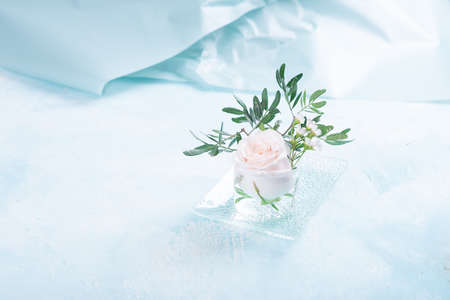 Pink rose in glass vase on blue background with vintage texture Stock fotó