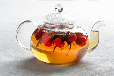Hot tea with rosehip in a glass transparent kettle on a light background