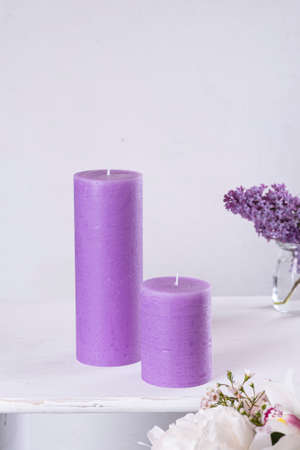 On the table are purple candles and a flower