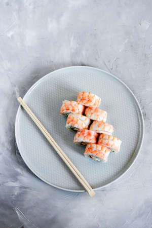 Japanese sushi close-up. Top view on white plate, light gray textured background.