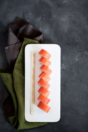Japanese sushi close-up. Side view of a white plate, dark gray textured background. Stock fotó