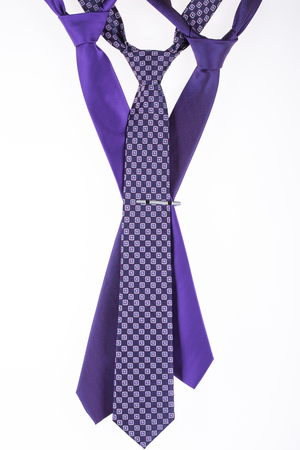 three purple tie on a white background with a tie clip Stock Photo