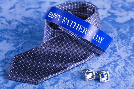 Blue tie and cufflinks on a blue marble background for the holiday Fathers Day