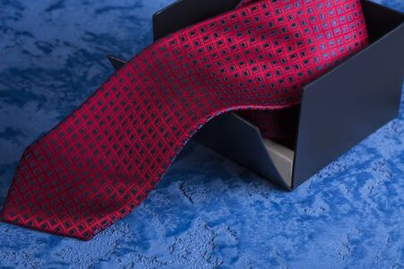 Red tie with a blue pattern on a blue background Stock Photo