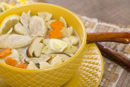 Italian soup with noodles, mushrooms and chicken in a yellow plate Stock Photo