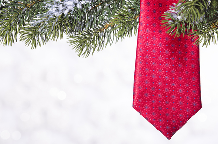 Tie on spruce branch on the background of snowflakes Stock Photo